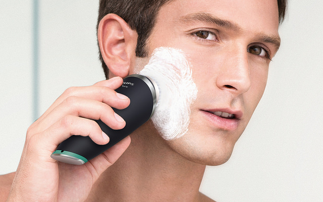 handsome young male using facial cleansing brush